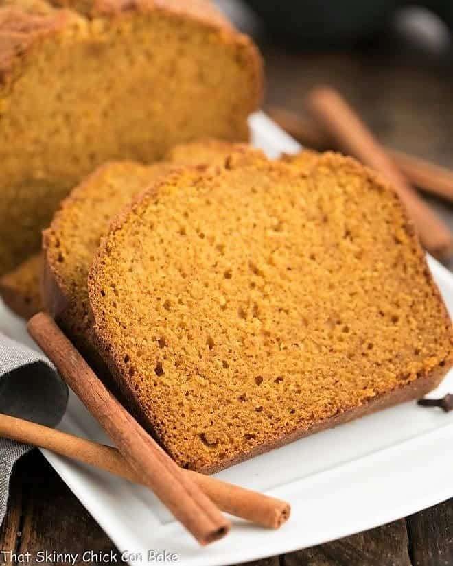 Classic Pumpkin Bread with cinnamon sticks on a white tray