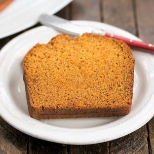 Classic Pumpkin Bread slice on a white plate with a knife