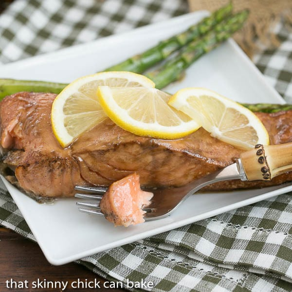 Grilled Asian Salmon bite on a fork along with a serving of salmon garnished with lemon
