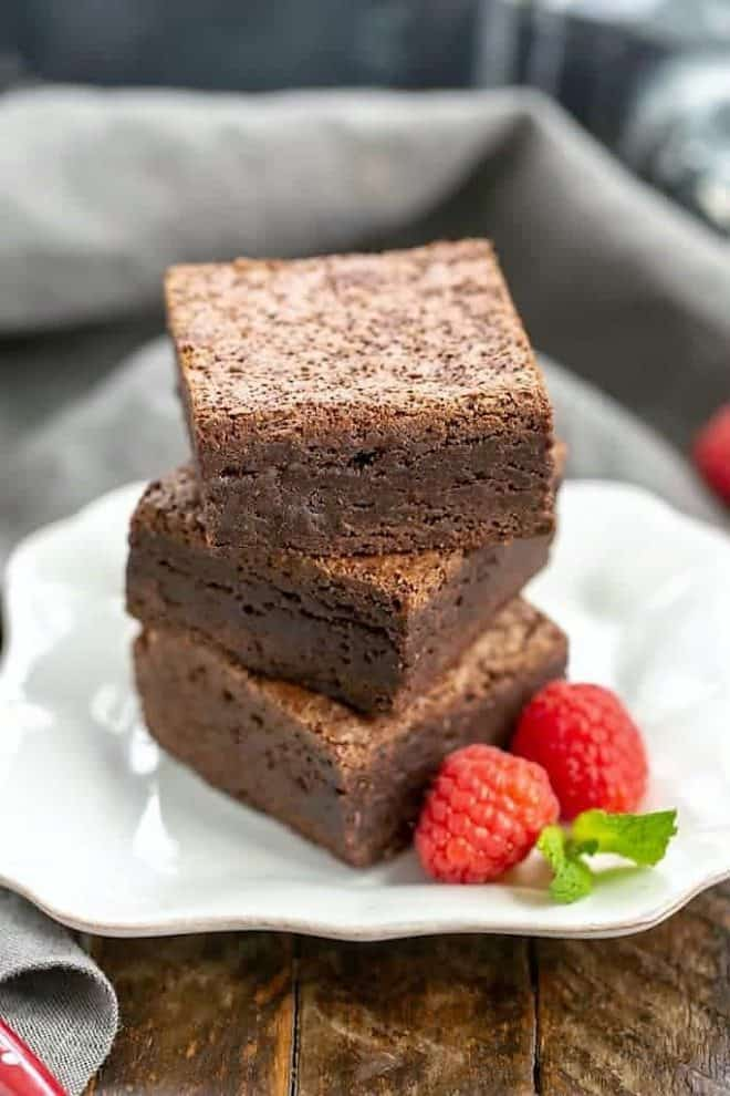 Stack of rich fudgy cocoa brownies on a square white plate