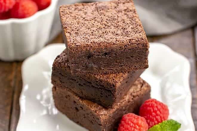 3 Rich Fudgy Cocoa Brownies stacked on a white plate