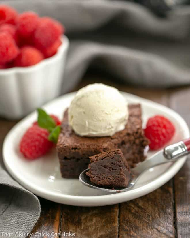 Rich Fudgy Cocoa Brownies on a white plate with a spoon and scoop of vanilla ice cream
