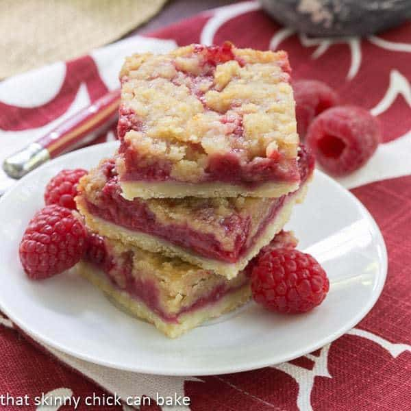 Streusel Topped Raspberry Squares stacked on a small white plate with fresh raspberries