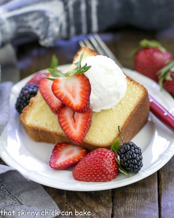 The Best Pound Cake slice topped with berries and cream