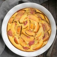 Fresh Peach Clafoutis in a white pie plate from above