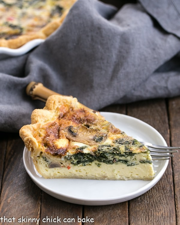 A slice of Spinach Mushroom Quiche on a white plate