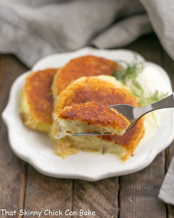 Gruyere Potato Cakes  with a bite on a fork in the foreground