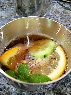 Pimm's Cup in a pewter cup with citrus, mint and cucumber garnish