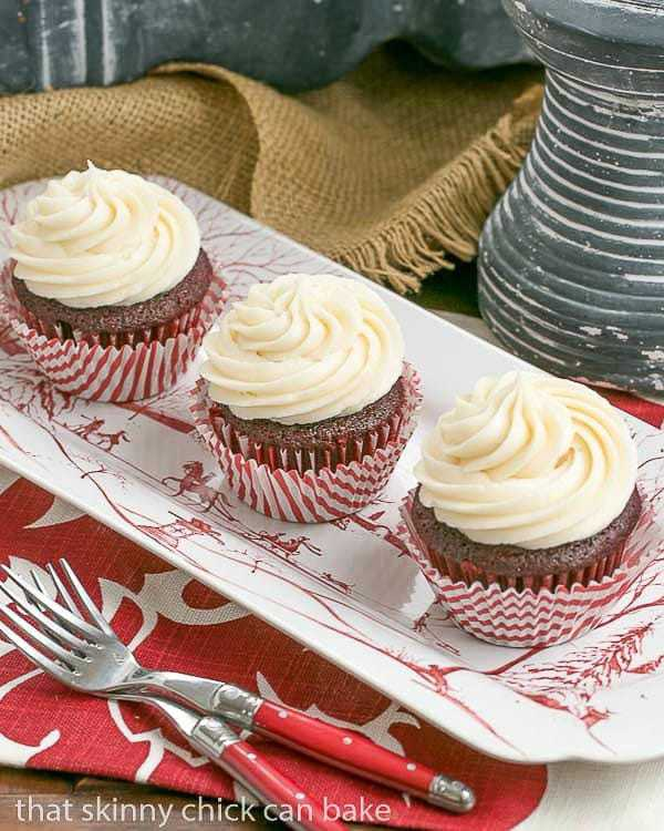 Three Red Velvet Cupcakes lined up on a red and white tray