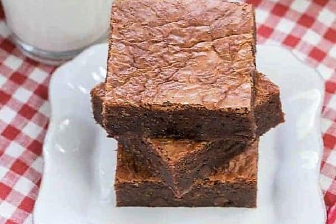 Fat Witch Brownies stacked on a square white plate over a checkered napkin