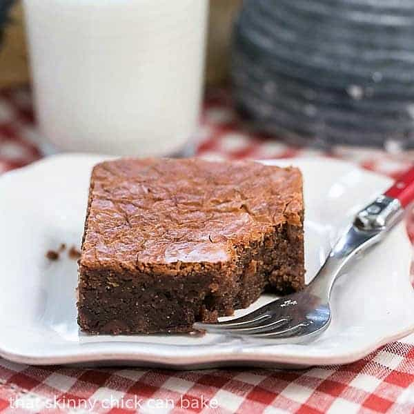 One Fat Witch Brownie on a white plate with a red handled fork with a bite removed