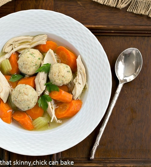 Overhead view of Chicken Soup with Matzoh Balls AKA Jewish Penicillin in a white soup bowl with a spoon