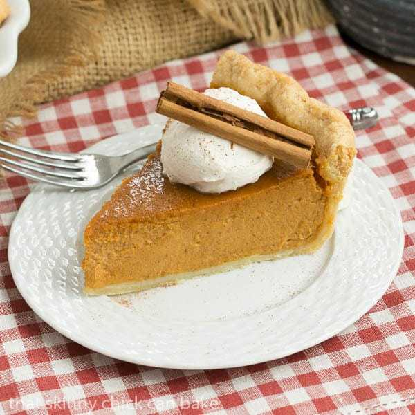 Classic Pumpkin Pie slice garnished with whipped cream and a cinnamon stick