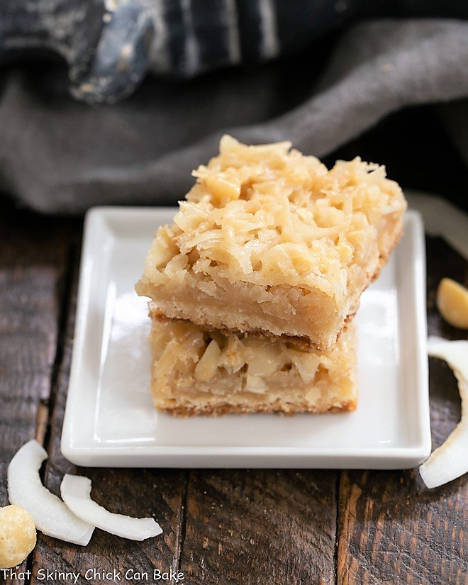 Coconut Macadamia Nut Bars stacked on a square white plate
