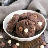 Quadruple Chocolate Cookies in a white bowl surrounded by chocolate chips