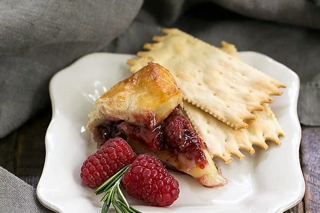 Slice of baked brie on a square white plate with crackers