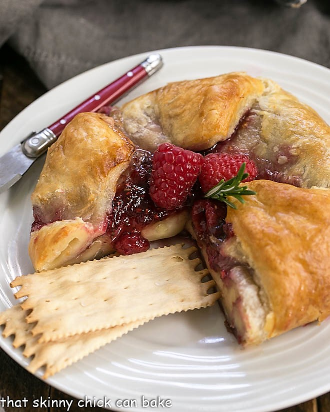 Raspberry Brie en Croute on a serving plate with crackers and a red handled knife