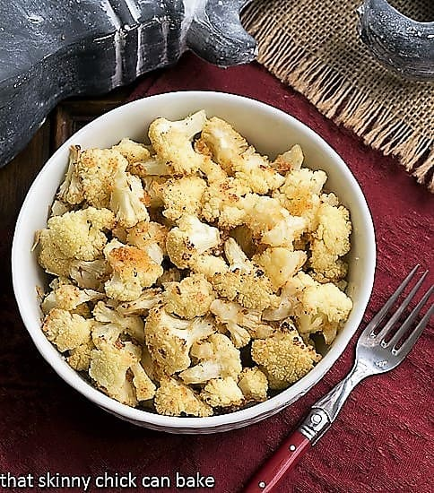 Overhead view of Roasted Cauliflower with Parmesan and Bread Crumbs in a round white bowl on a red napkin