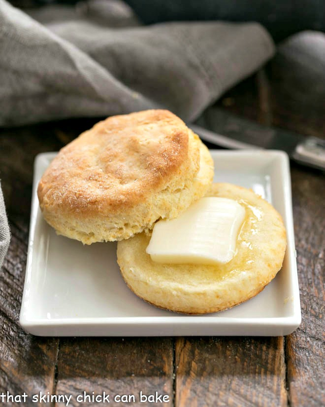 Split buttermilk biscuit with a pat of melting butter on a square white plate