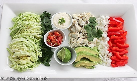 Grilled fish tacos and fixings on a white platter
