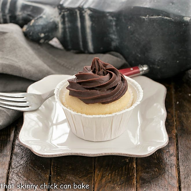 A boston Cream Pie Cupcake on white square plate with a red handled fork