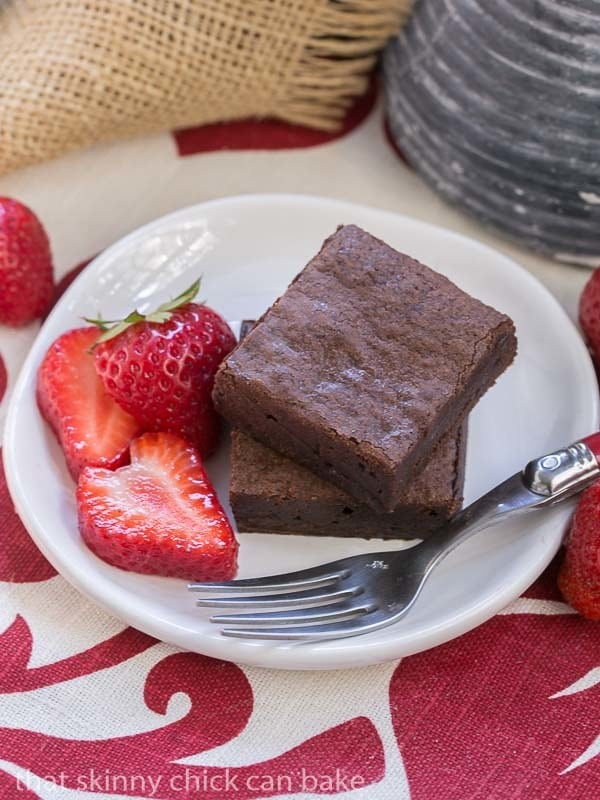 Cocoa Brownies with Browned Butter on a white round plate with a red handled fork