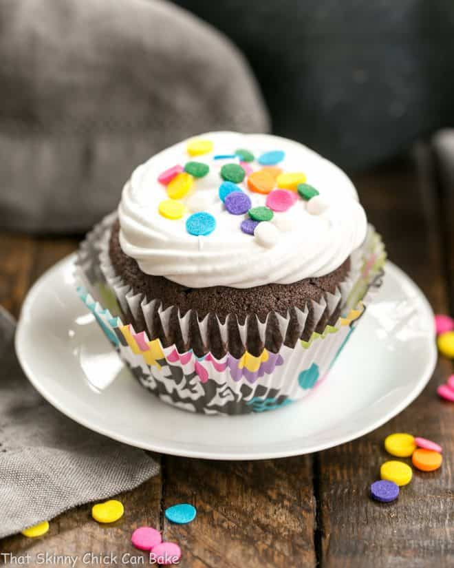 Cocoa Cupcakes with Ganache Filling on a small white plate topped with sprinkles
