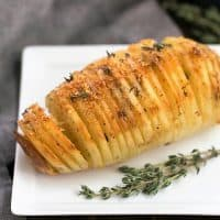 Hasselback potato on a white plate with a sprig of thyme