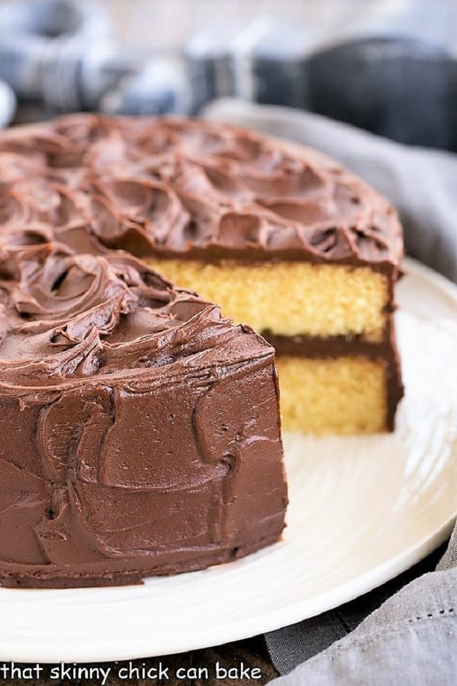 Perfect Yellow Cake Recipe with Chocolate Buttercream on a white cake plate with a slice removed