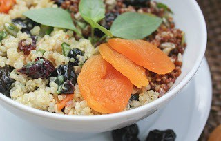 Close up of Quinoa, Fruit and Nut Salad in  a white bowl on a white plate