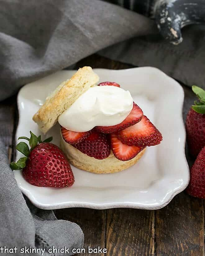 Classic Strawberry Shortcakes on a square white plate with a half strawberry garnish