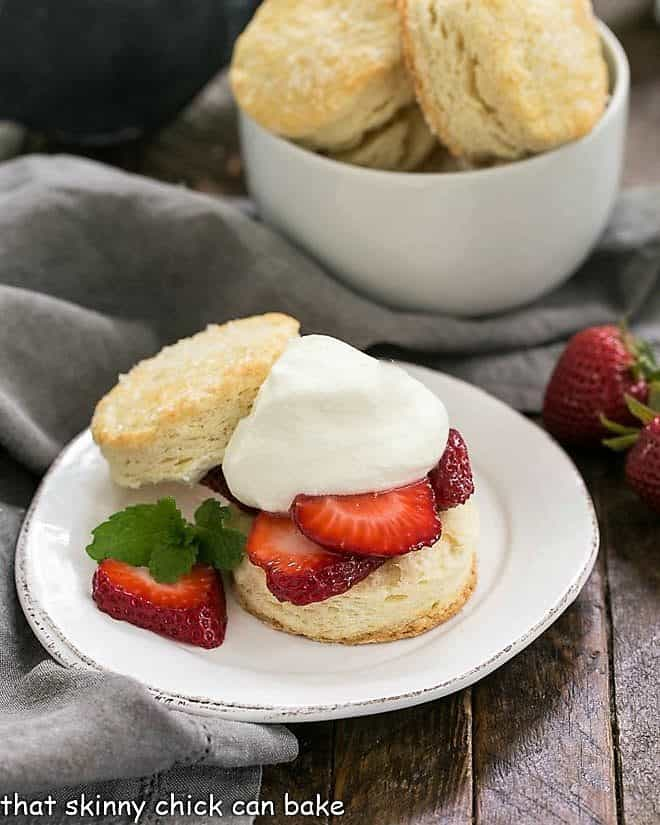 Classic strawberry shortcake on a plate in front of a bowl of shortcake biscuits