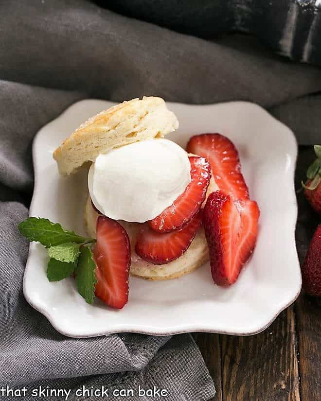 Classic Strawberry Shortcake on a square white plate with a dollop of cream and mint sprig