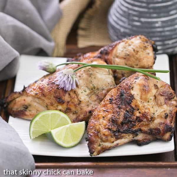 Grilled Thai Chicken on a square white plate garnished with lime wedges and chives
