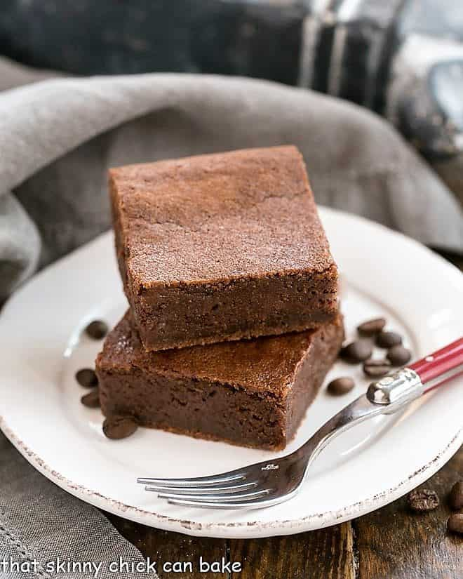 Kahlua Brownies on a round white plate with coffee beans and a fork