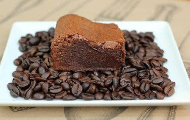 Kahlua Brownies on a white plate covered with coffee beans