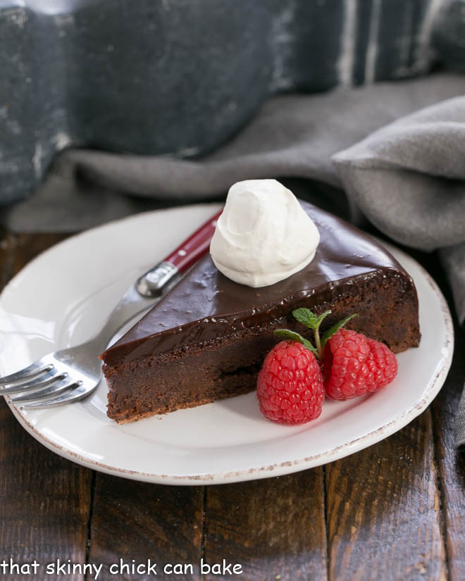 Slice of Flourless Chocolate Cake with Ganache Topping garnished with whipped cream and berries