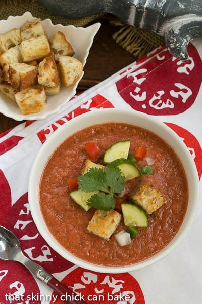 Classic Gazpacho with Homemade Croutons in a white bowl topped with cucumbers, peppers and croutons