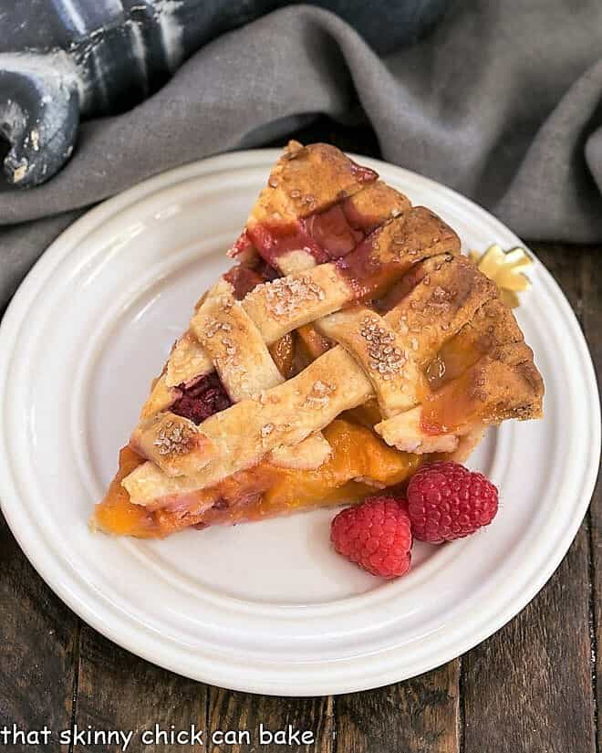 Overhead view of Peach raspberry pie slice on a white dessert plate