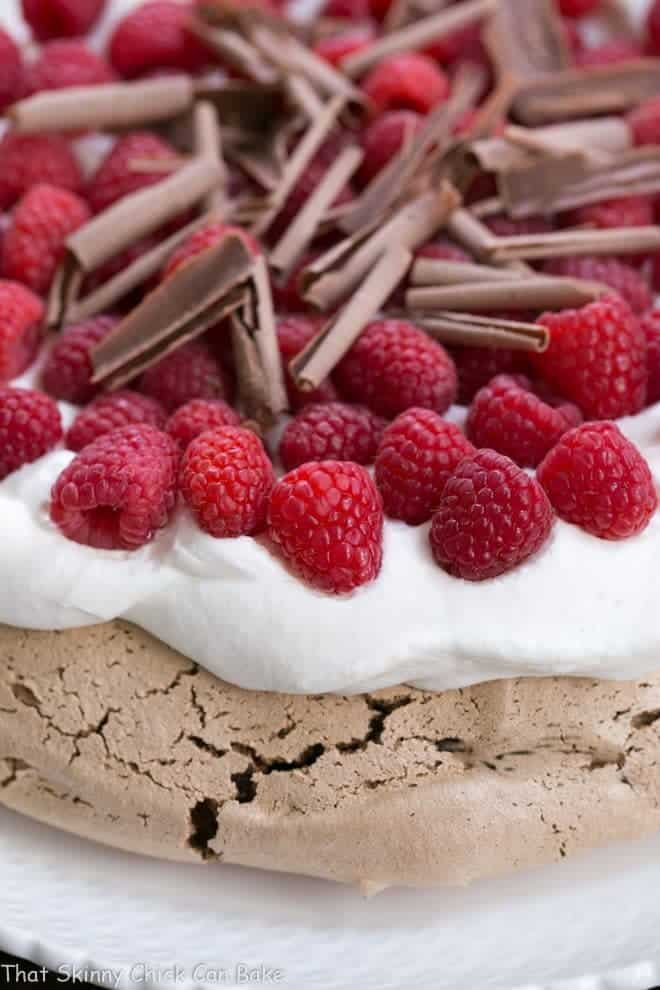 Edge of a Chocolate Raspberry Pavlova topped with chocolate shavings