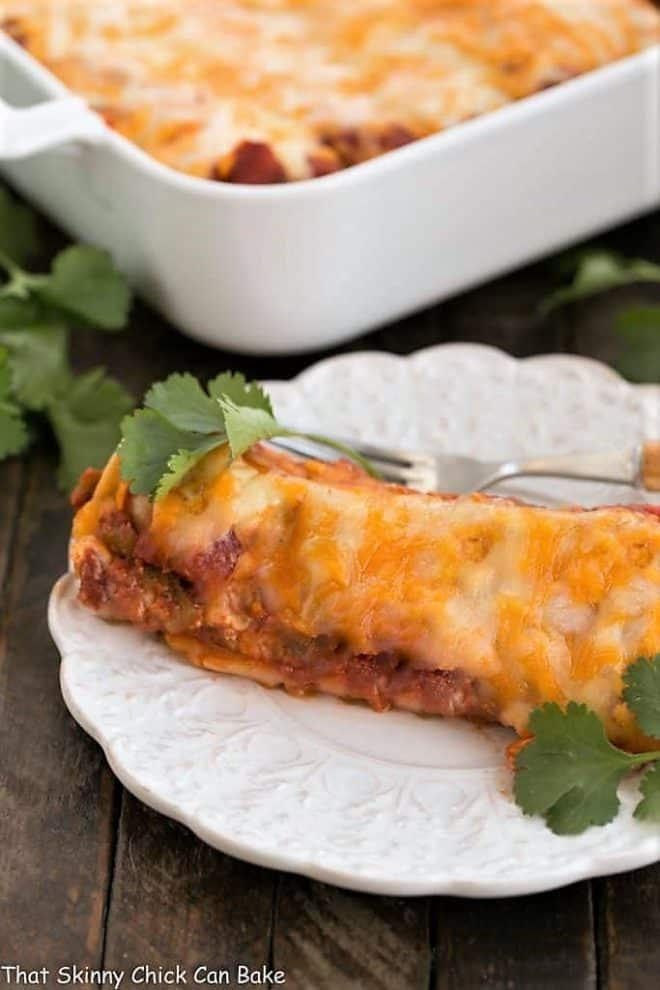 Cheesy Chicken Enchiladas  on a plate with a casserole dish in the background