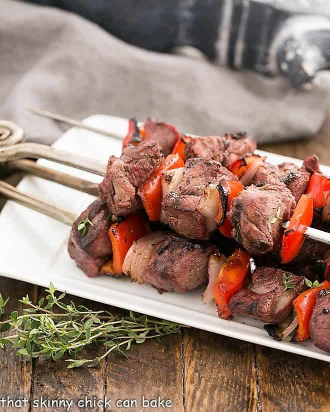 Marinated Greek Lamb Kebabs on a white serving tray with thyme garnish