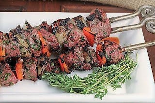 Greek kabobs on a white tray with thyme