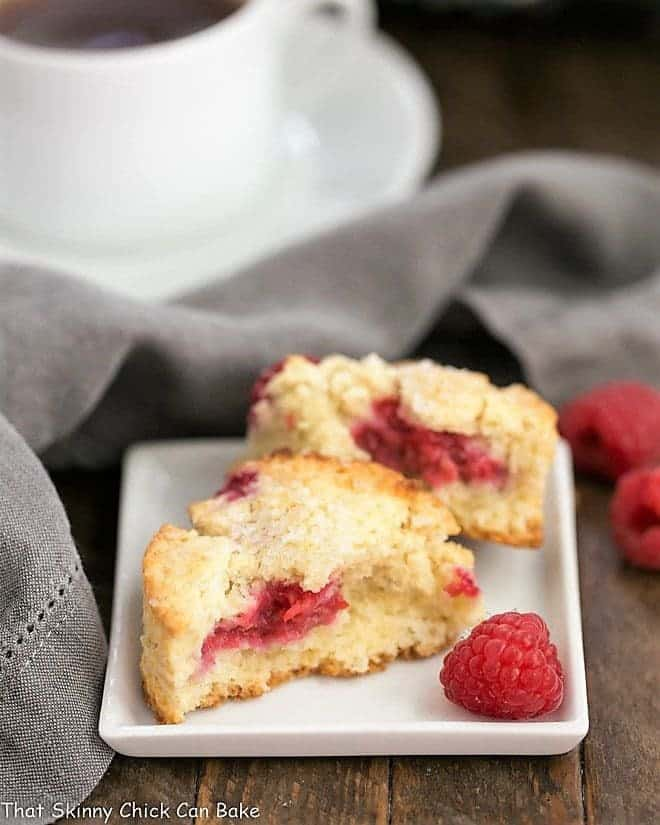 Raspberry Cream Scones on a white plate with a raspberry garnish