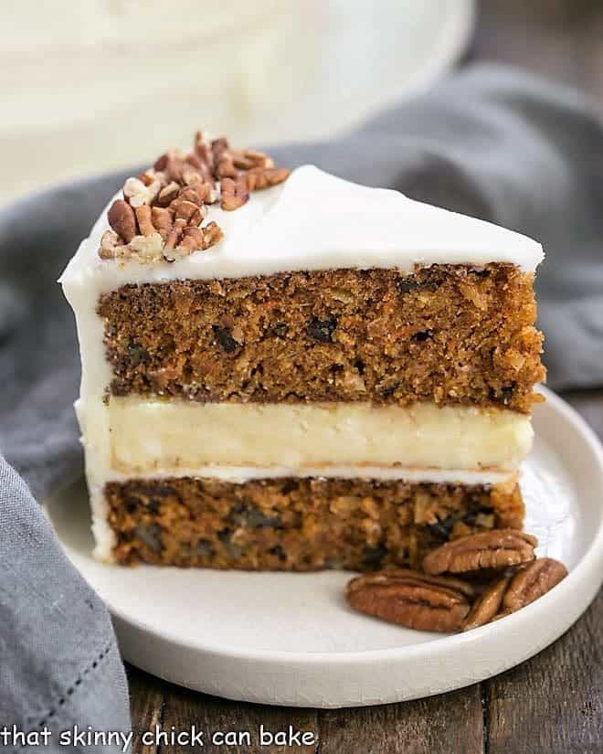 Slice of Cheesecake Filled Carrot Cake on a rimmed white plate with pecans