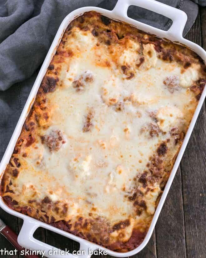 Ricotta Lasagna with Sausage in a white rectangular baking dish