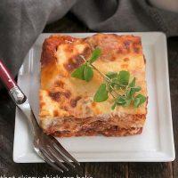 A slice of ricotta lasagna on a square white plate