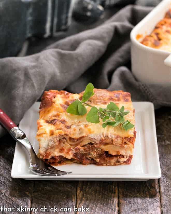 A slice of Sausage Ricotta Lasagna on a white plate with a sprig of oregano