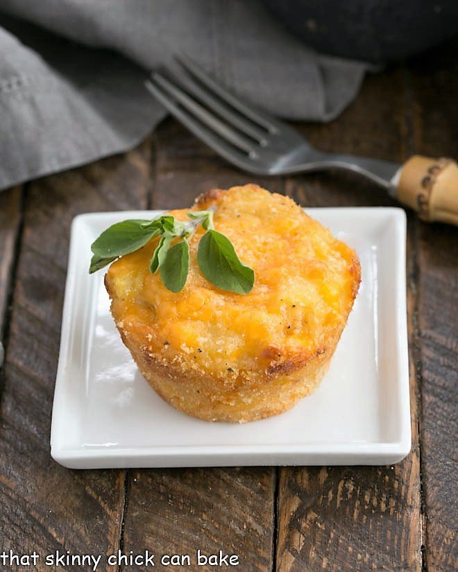 Cheesy Potato Cup on a square white plate with a sprig of herbs to garnish