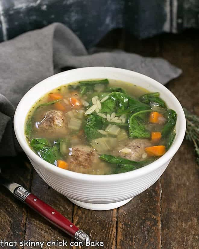 Italian Wedding Soup in a white bowl with a red handled spoon